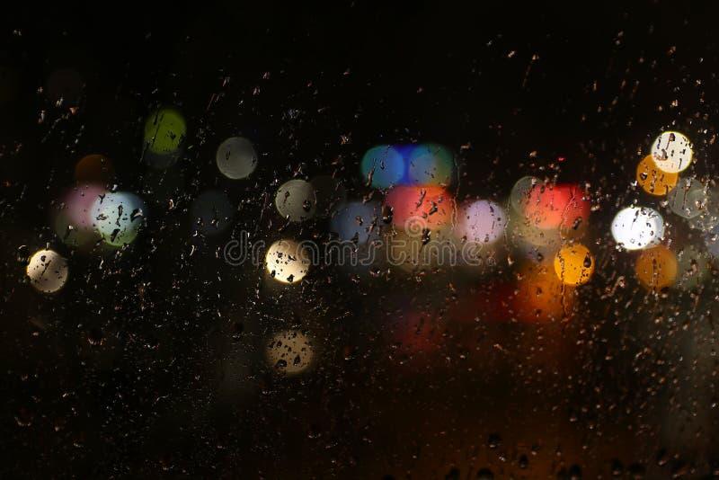 上色在多雨黑暗的玻璃窗的光 库存图片