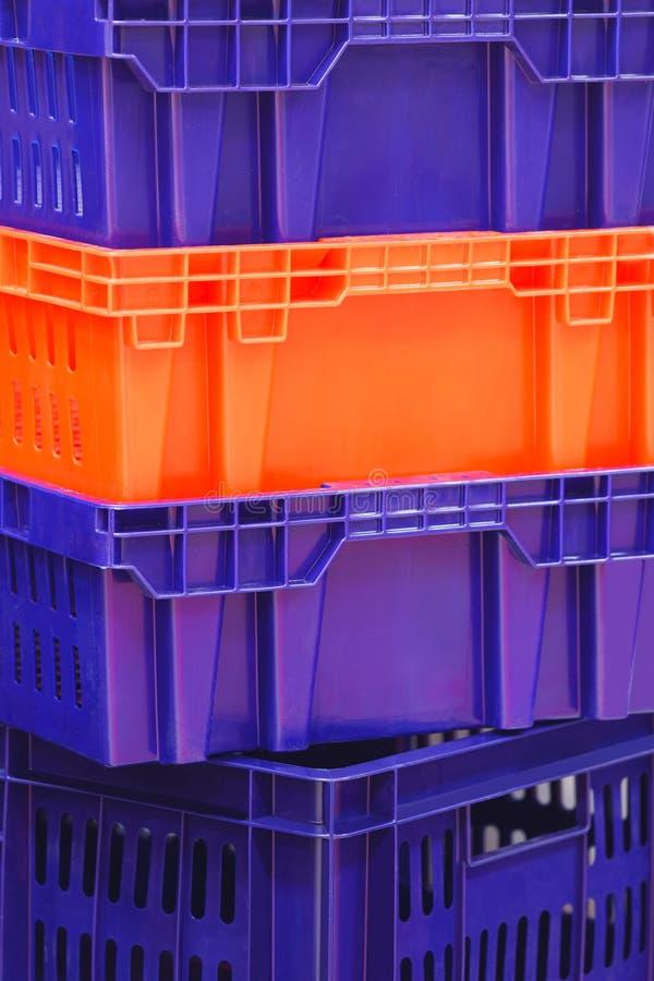 上色塑料盒蓝色橙色或红色在彼此 免版税库存图片