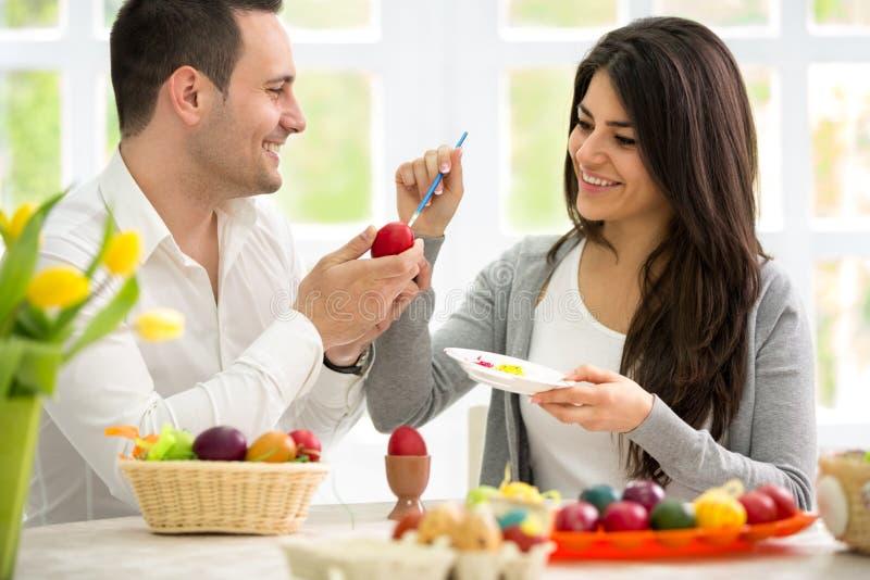 上色复活节彩蛋的愉快的夫妇 免版税库存图片