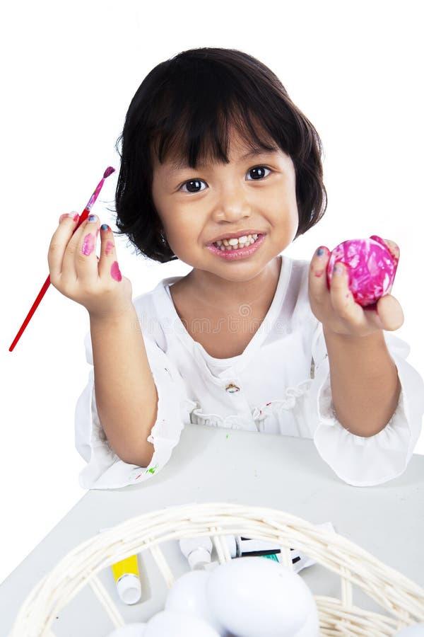 上色复活节彩蛋的逗人喜爱的小女孩 免版税库存照片