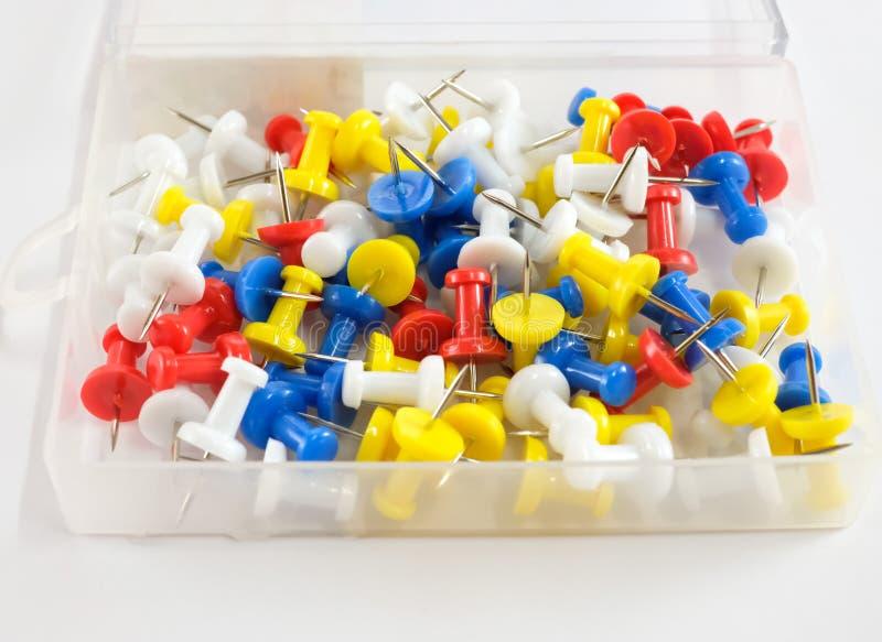上色推挤别针在塑料盒的红色,黄色,白色和蓝色小组在白色背景 免版税库存照片