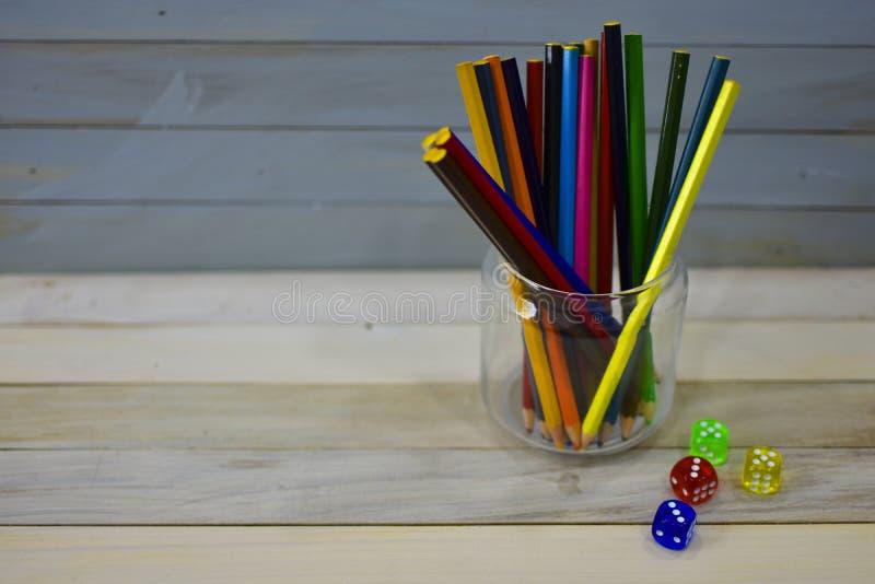上色铅笔玻璃瓶子五颜六色的丙烯酸酯的模子木土气背景 库存照片