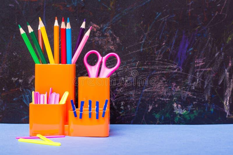 上色铅笔,剪刀,计数棍子和夹子在玻璃 免版税库存照片
