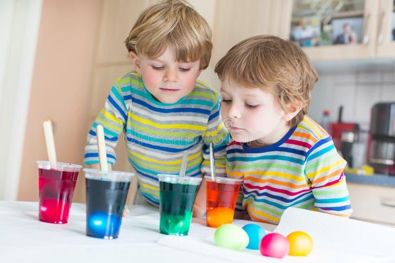 上色鸡蛋的两个小白肤金发的孩子男孩为复活节假日 免版税库存照片