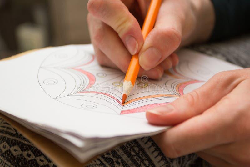 上色- antistress与橙色铅笔 疗法解除重音 库存照片