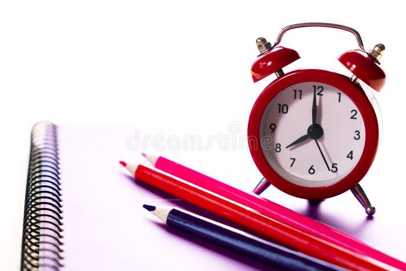 上课时间minimalistic概念 色的铅笔和笔记本和一个红色闹钟 免版税库存图片