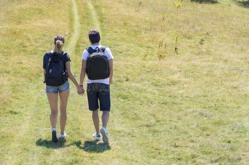 上道路的远足者夫妇对山 库存图片