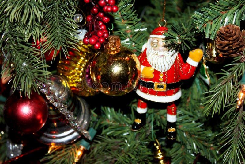 上釉圣诞老人和其他装饰品在传统圣诞树 免版税库存图片