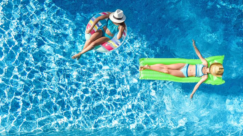 上面游泳场空中寄生虫视图fom的孩子,愉快的孩子在可膨胀的圆环多福饼游泳,并且床垫,女孩获得乐趣 免版税库存图片