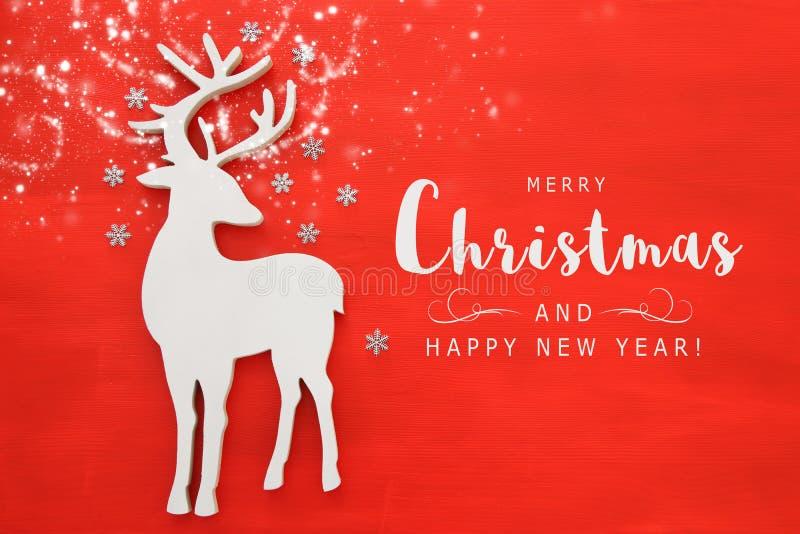 上面竞争白色木圣诞节鹿的图象在红色背景的 平的位置 库存图片