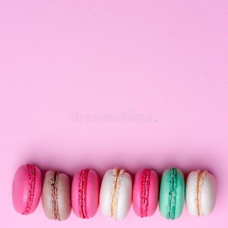 从上面结块macaron或蛋白杏仁饼干在绿松石背景,五颜六色的杏仁饼,淡色,葡萄酒卡片,上面 库存照片