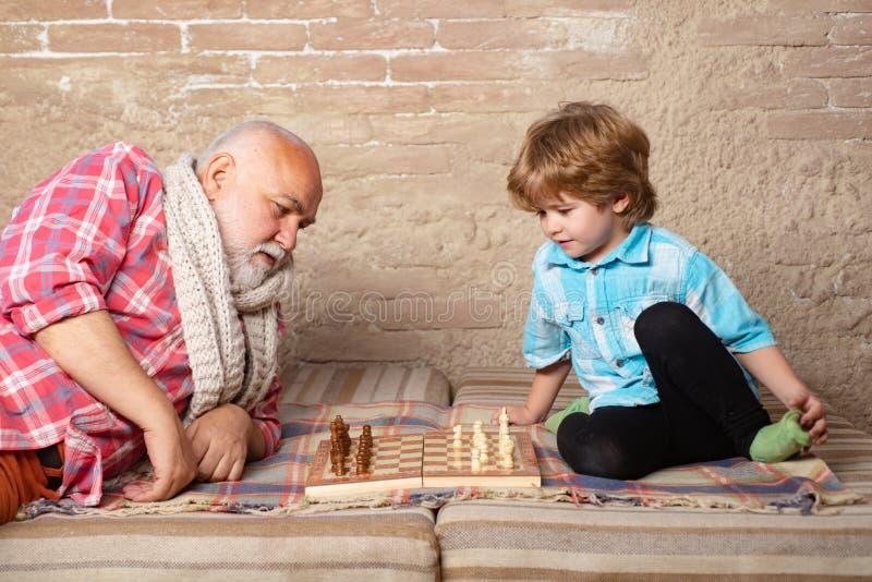下与他的祖父的小男孩棋 ?? 考虑他的在一盘棋的接下来的步骤的老人 免版税库存图片