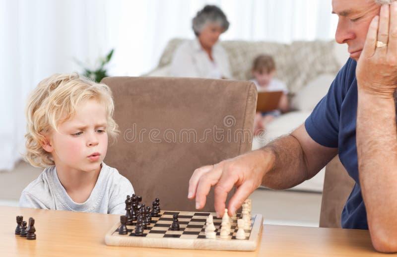 下与他的祖父的新男孩棋 免版税库存图片