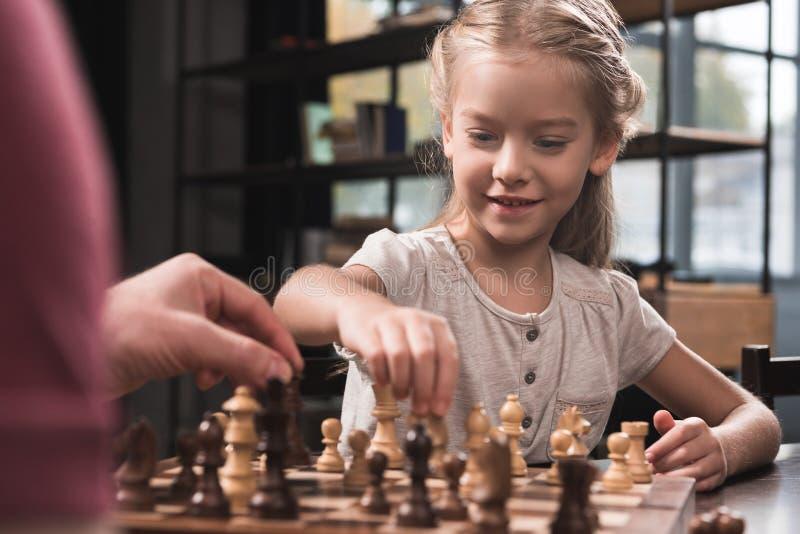 下与她的父亲的学龄前儿童孩子棋 免版税库存图片