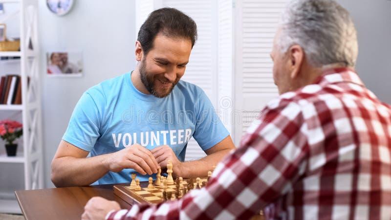 下与年长人的中间年迈的男性志愿者棋在老人院,爱好 免版税库存照片