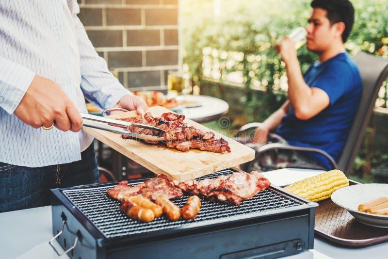 下午党享用小组的朋友喝与烤肉的啤酒和愉快的烤肉,当享受家庭党时 免版税库存照片
