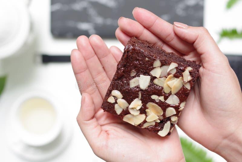 下午茶时,享用美味的自制坚果巧克力蛋糕和伯爵灰 在美丽的手上 免版税图库摄影