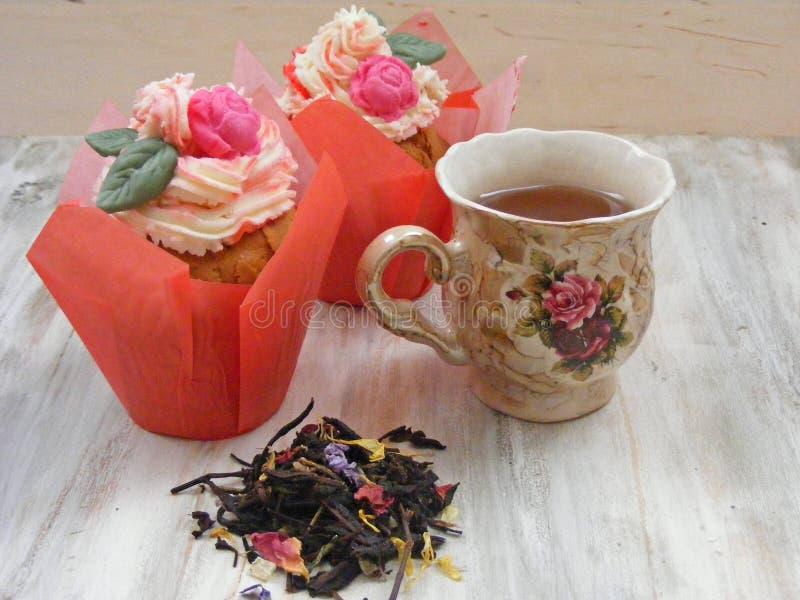 下午茶用在葡萄酒茶杯ans酿造的玫瑰杯形蛋糕在破旧的桌上 免版税库存照片