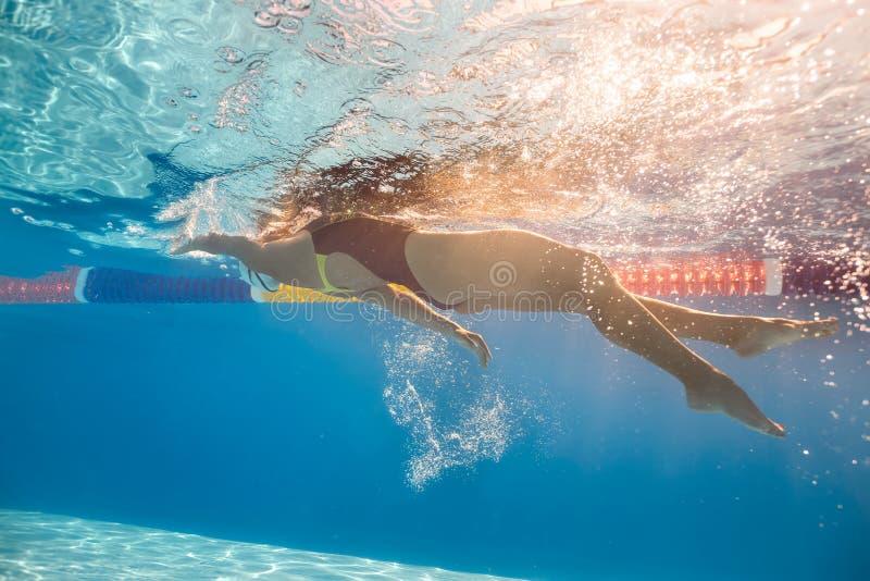 水下后面爬行的样式的游泳者 免版税库存图片