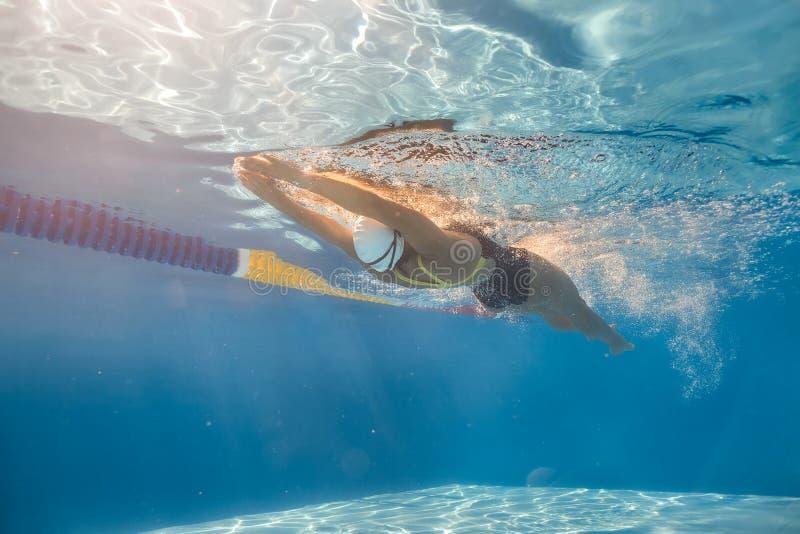 水下后面爬行的样式的游泳者 免版税库存照片