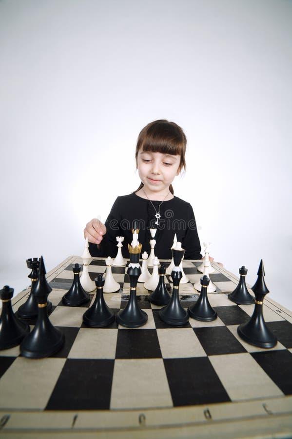 下在白色的小女孩棋 免版税库存照片