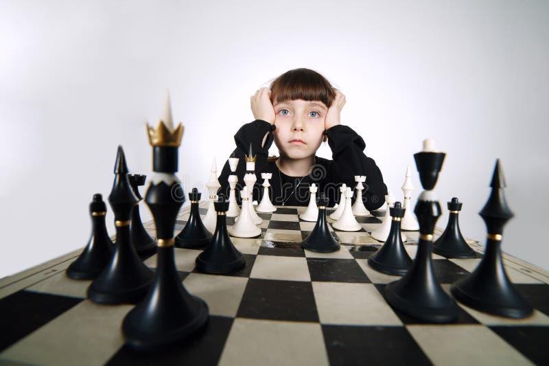 下在白色的小女孩棋 图库摄影