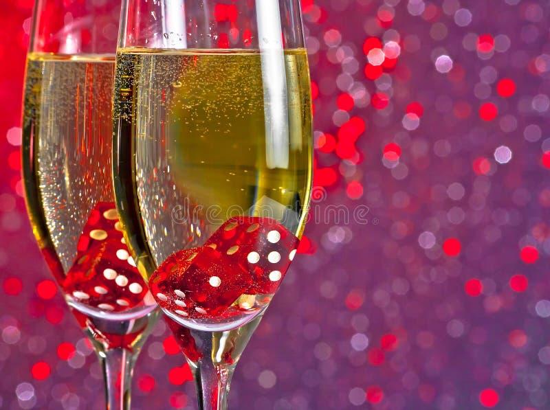 滴下在红色和紫罗兰色色彩光bokeh背景的香槟槽的红色模子 库存照片