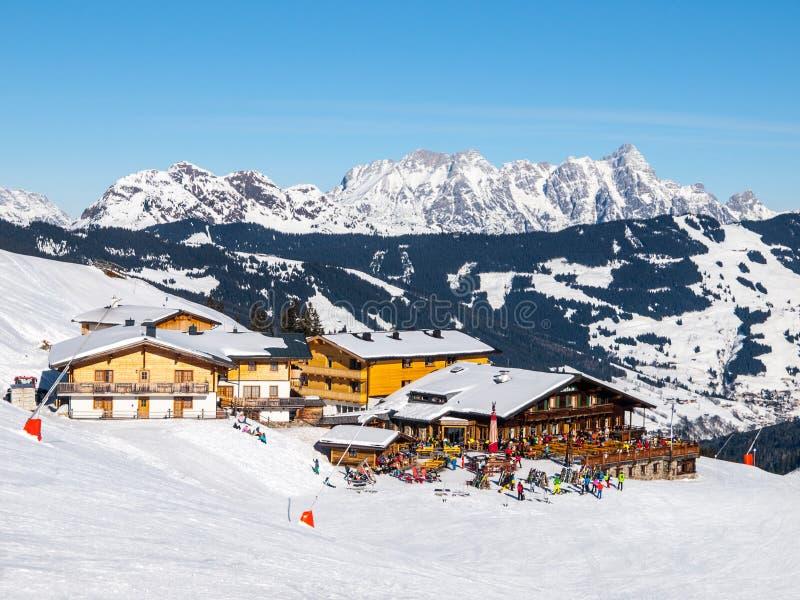 下坡倾斜和滑雪后的山小屋与餐馆大阳台在萨尔巴赫Hinterglemm Leogang冬天依靠,提洛尔 免版税库存图片