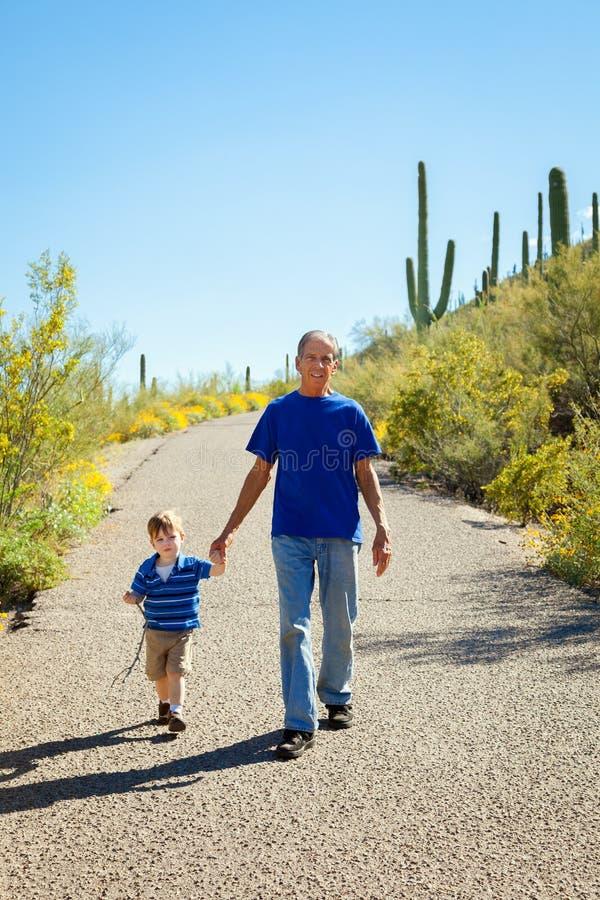 下坡祖父和年轻孙子远足,握在a的手 免版税库存照片