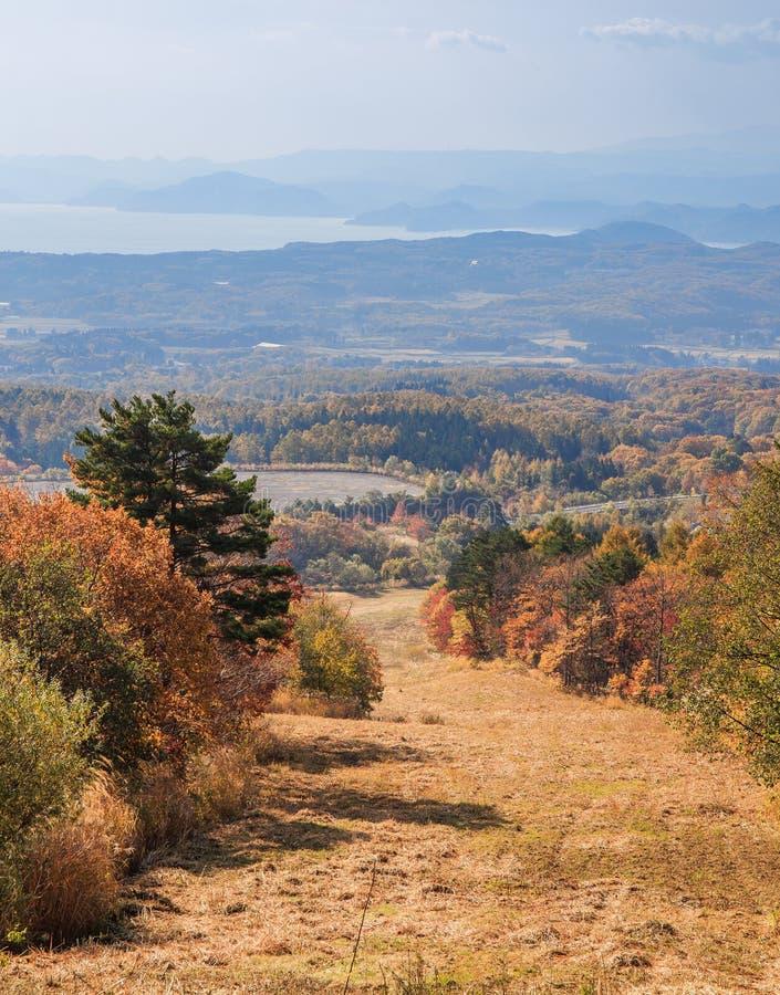 下坡道路和自然风景在秋天在磐梯圣金线路-磐梯,福岛,日本 图库摄影