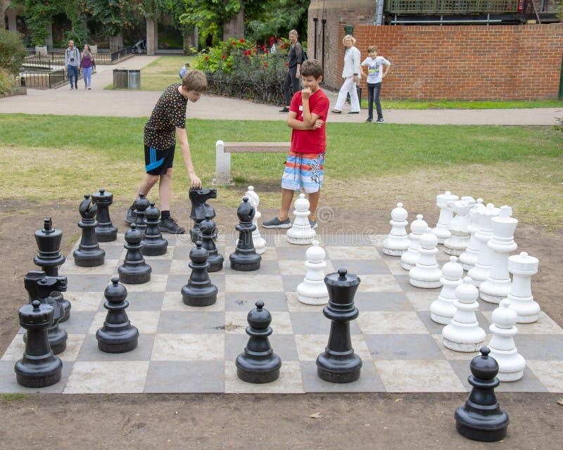 下室外棋的两个年轻男孩 免版税库存照片