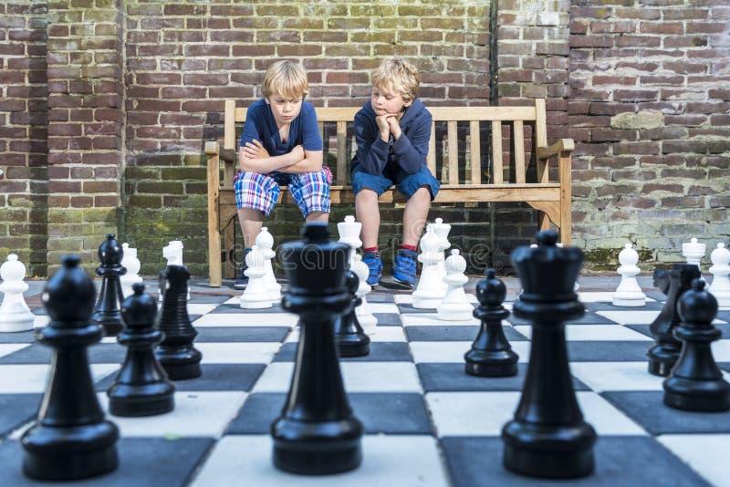 下室外棋的男孩 免版税库存照片