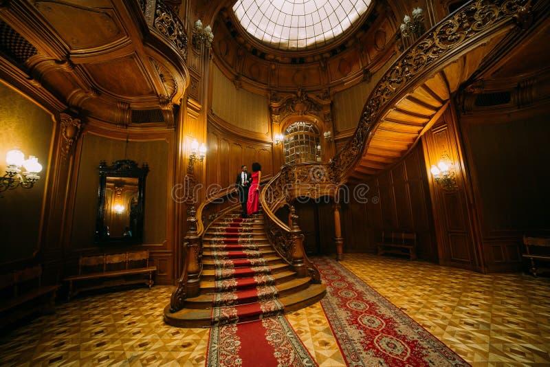 去下来在葡萄酒台阶的美好的非洲夫妇 豪华剧院内部背景 库存照片