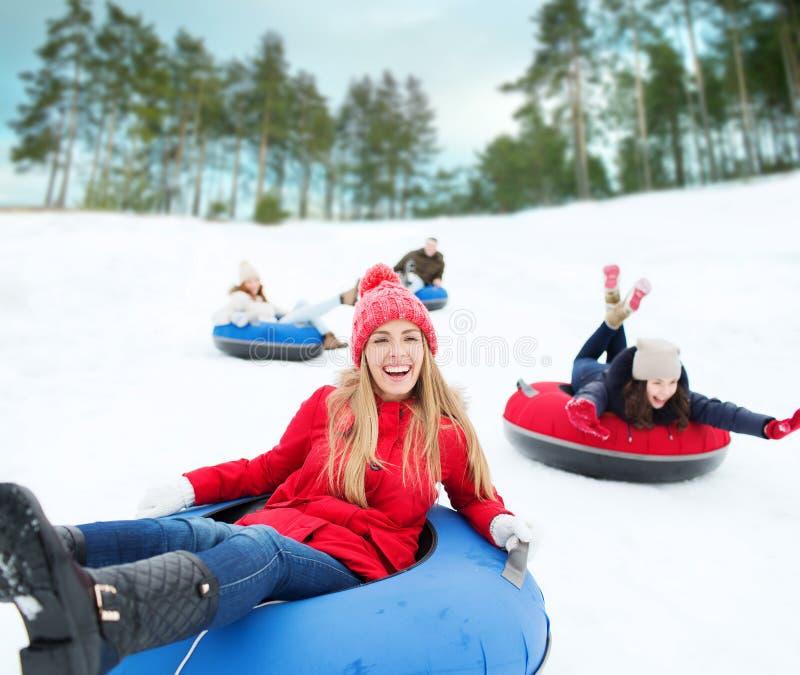 滑下来在雪管的小组愉快的朋友 库存照片