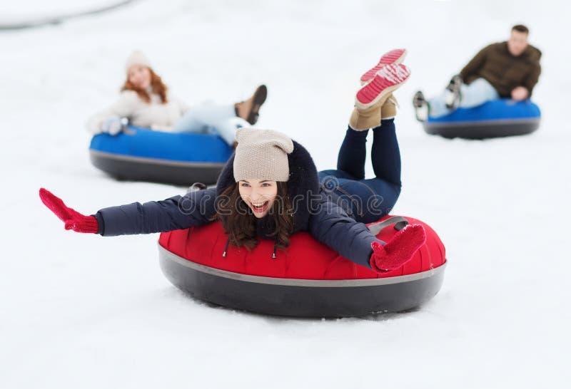 滑下来在雪管的小组愉快的朋友 免版税图库摄影