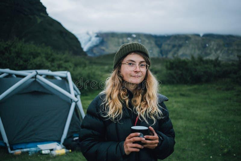 下来夹克的年轻女人在山野营 库存图片