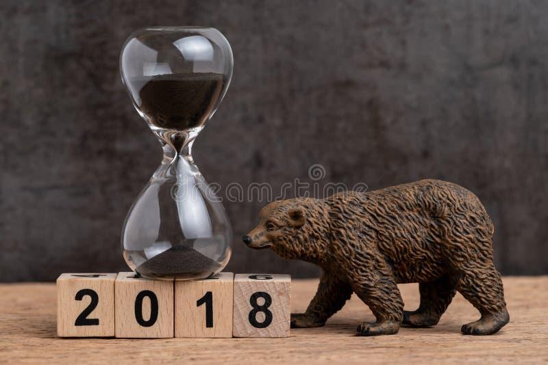 下来年终计数为2018财政或与sandglass或醒来滴漏和熊的形象的熊市概念在立方体块 库存照片