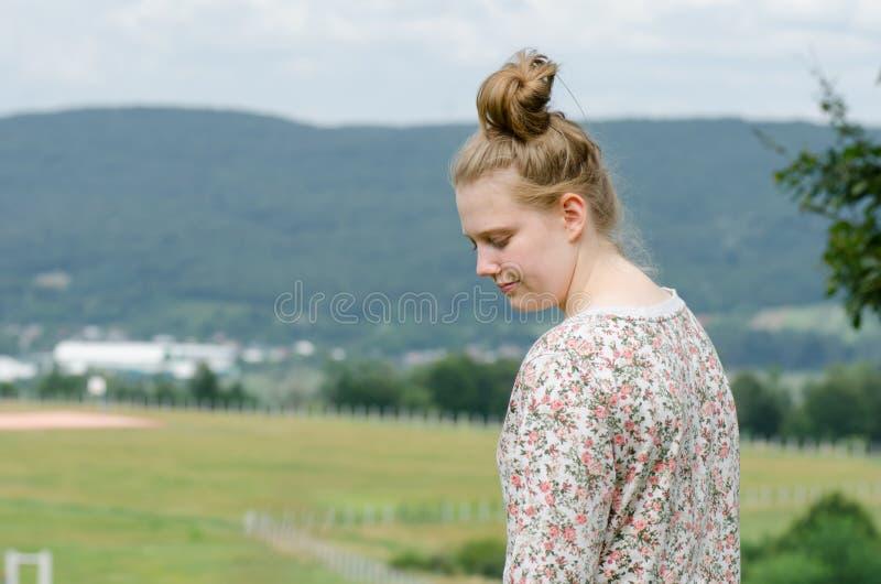 下来年轻白肤金发的妇女神色在山景 库存图片