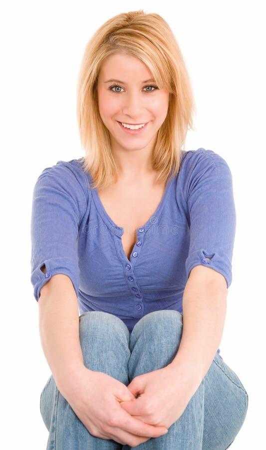 下来放松坐的微笑的美丽的金发碧眼的女人 免版税图库摄影