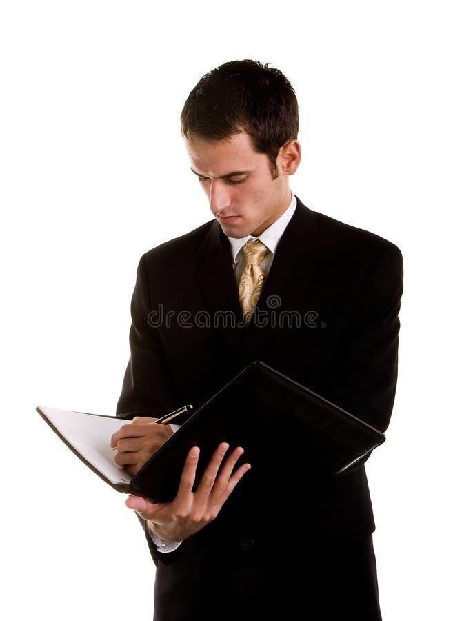 下来查找笔记本文字年轻人的生意人 免版税库存照片