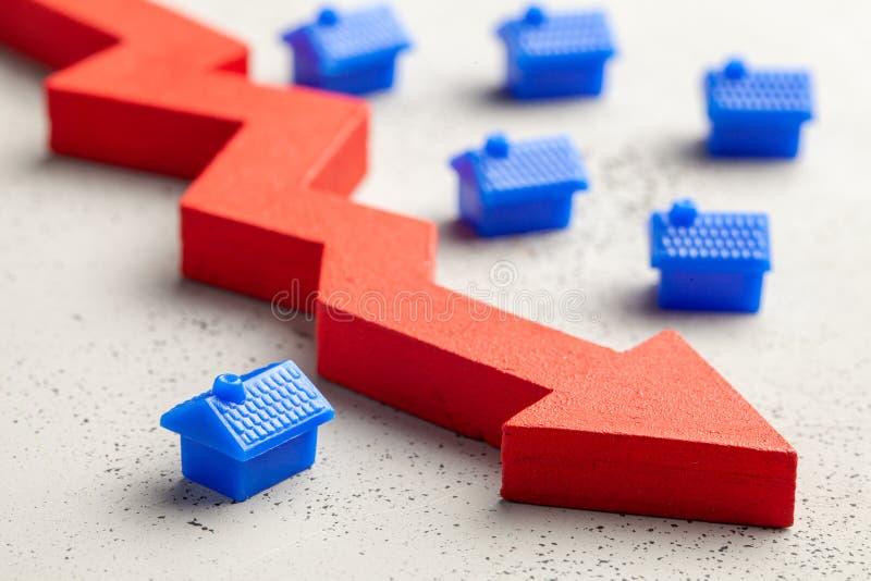 下来议院和红色箭头 下跌的不动产价格 减少的保险或税率 图库摄影