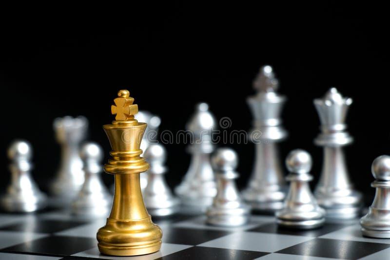 下棋比赛面孔的金国王与在黑背景的另一个银色队 图库摄影