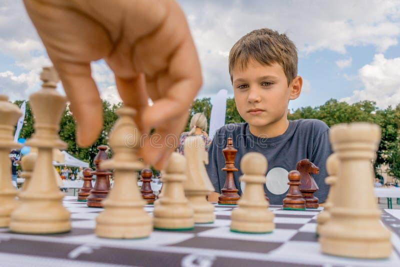 下棋的孩子在棋枰户外 苦苦思索在棋组合的男孩 免版税图库摄影