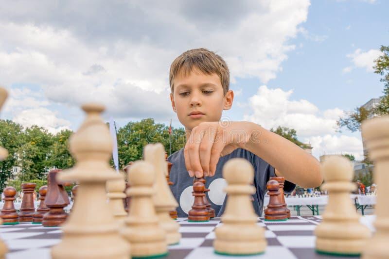 下棋的孩子在棋枰户外 苦苦思索在棋组合的男孩 库存图片