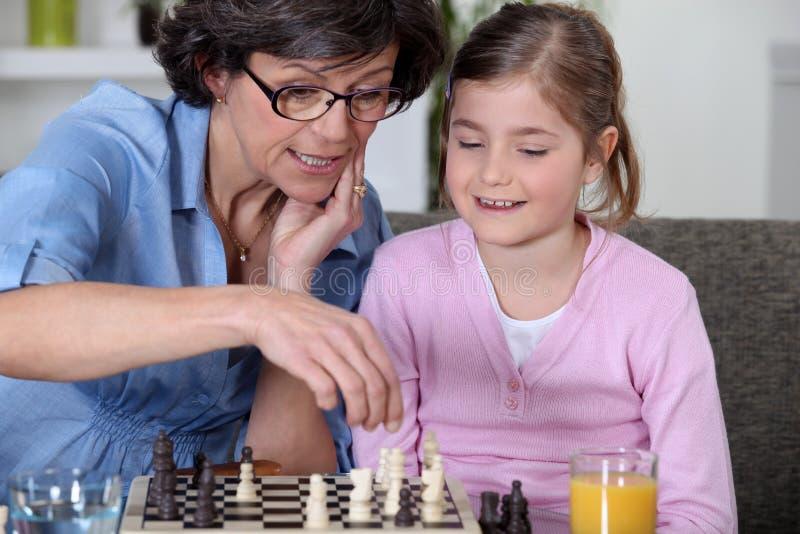 下棋的母亲和女儿。 免版税库存照片