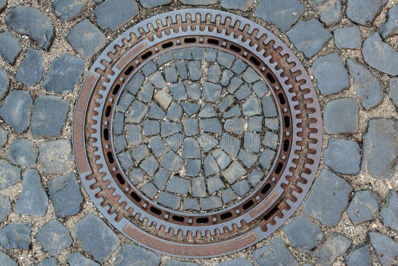 下水道出入孔的顶视图有铺路石背景 库存图片