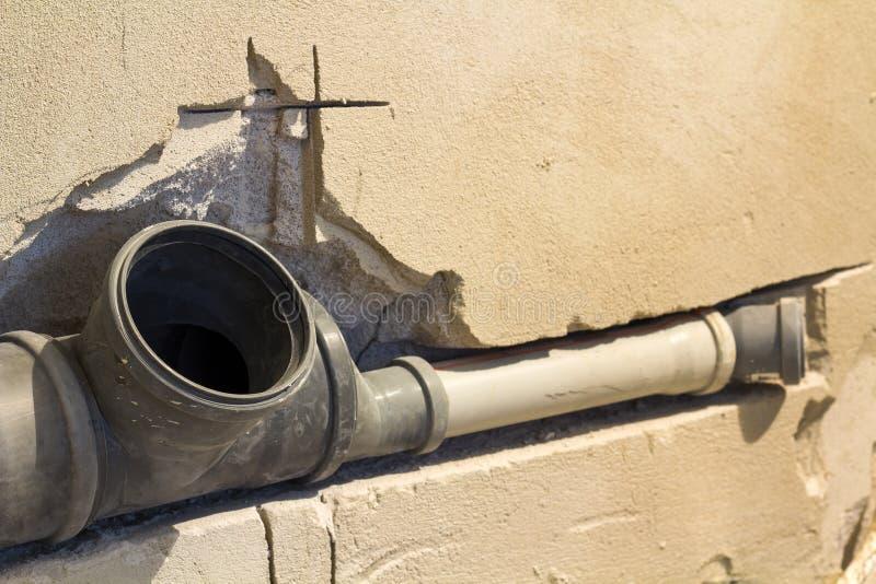 下水道的设施在公寓内部的卫生间里在改造工程期间的 使用的水的灰色塑料排水管 免版税图库摄影