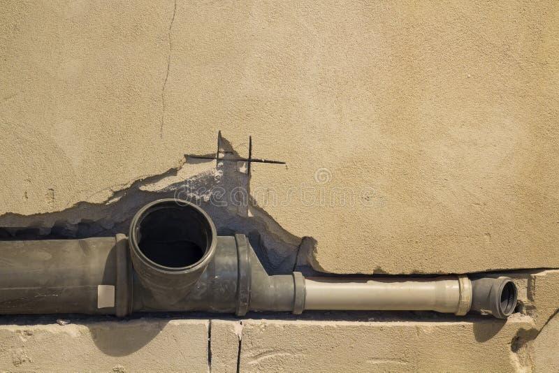 下水道的设施在公寓内部的卫生间里在改造工程期间的 使用的水的灰色塑料排水管 库存照片