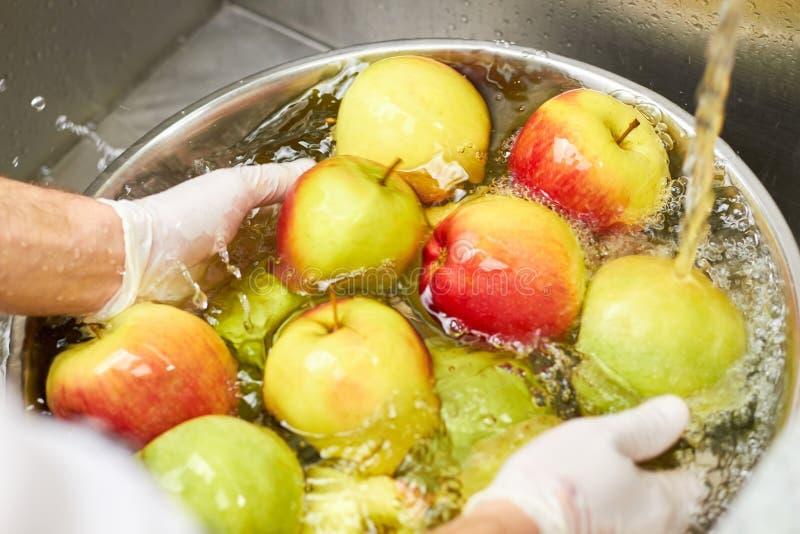 下沉和洗涤由厨师的苹果 库存图片