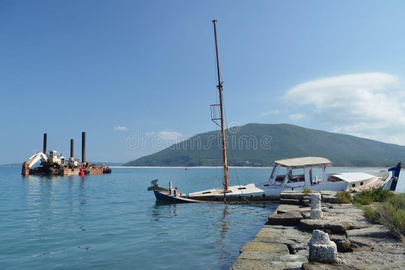 下沉的木小船和老生锈的撒粉瓶 免版税库存照片
